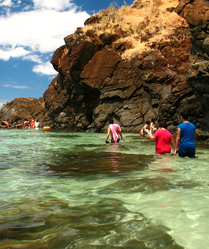 travelers wading through rocky beach at Anawangin Cove, San Antonio, Zambales