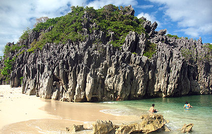 sandy beach and limestone rock at Lahos Island, Caramoan Peninsula, Camarines Sur