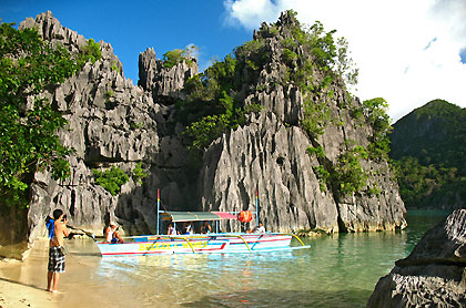 limestone karst formation and beach with docked boat at Minalahos Island
