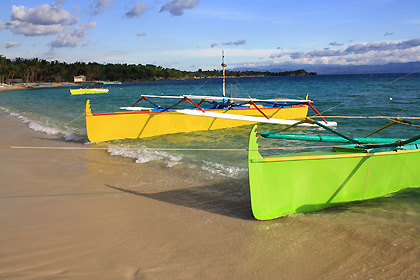 colorful boats on Tambobong Beach, Dasol, at sunset