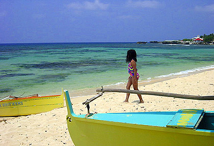 girl walking along Patar Beach with outrigger boat in the foreground, Bolinao, Pangasinan
